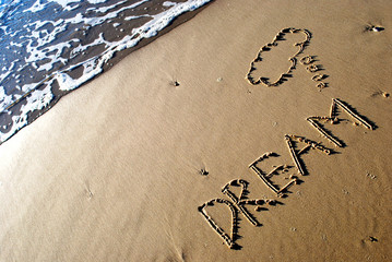 The word dream written in the sand