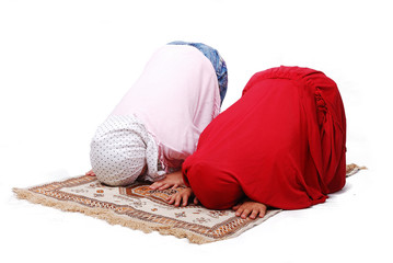 A young muslim girls in traditional clothes praying