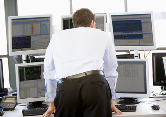 Stock Trader Looking At Multiple Monitors