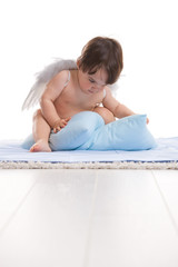 Little angel playing with pillows