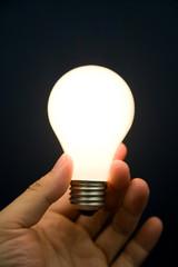 Hand holding a Bright Light Bulb