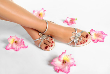 Beautiful woman legs with red manicure on the feet and flowers