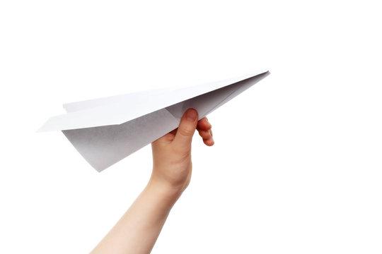 Child's hand launching white paper airplane