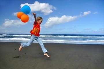 Fillette jouant sur une plage de sable noir avec des ballons.
