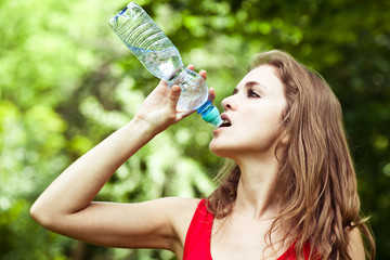 Girl drink water in park after volleyball game
