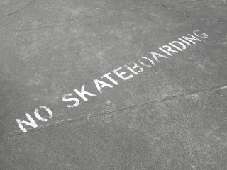 No Skateboarding sign painted on sidewalk