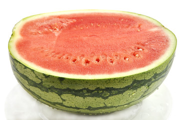 Cut watermelon with drops on plate isolated over white.