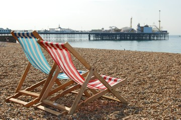 Deckchairs on Brighton beach and pier, England