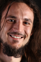 Portrait of smiling young man with long hair