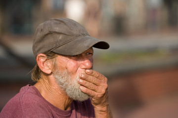 Homeless man with hand over mouth