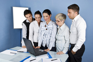Staff of business people in office using laptop