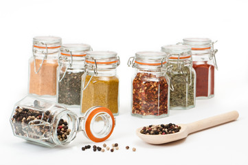 Spoonful of tropical peppercorns and filled spice jars