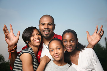 Happy African American family, father with teenage daughters.