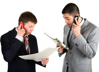Two young businessmen working and telling the phone