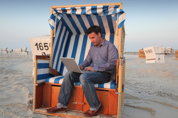 Junger Mann mit Laptop und Computer am Strand