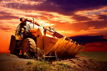 Wall Mural - Yellow tractor on golden surise sky
