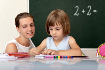 Elementary school pupil working under with teacher