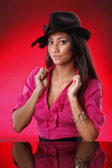Cute teen with black hat on red