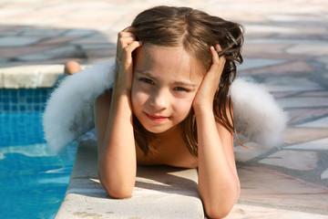 petit ange posé au bord de la piscine