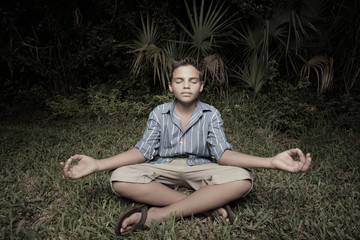 Young boy meditating in a field at night