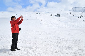 Senior woman taking picture in winter mountains
