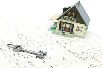A model home and house key on architectural plans