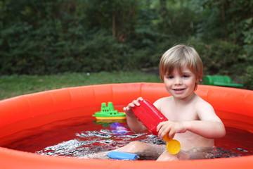 Kleiner Junge im Planschbecken im Garten