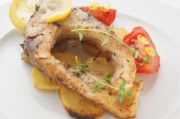 grilled carp fillet on organic potato with lemon