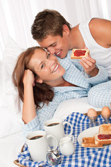 Young happy couple having home made breakfast in bed
