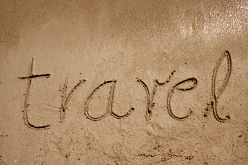 Travel handwritten in sand on a beach