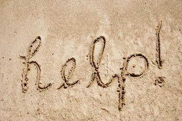 Help handwritten in sand on a beach