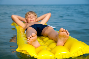 Young boy swimming on mattress in the sea