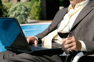 Businessman with laptop and glass of red wine