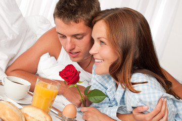 Happy man and woman having breakfast in bed together