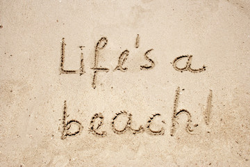 Life`s a beach handwritten in sand for natural,