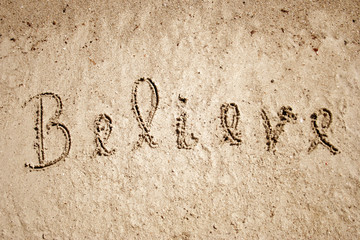 Believe handwritten in sand for natural