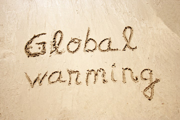 Global warming handwritten in sand for tourism