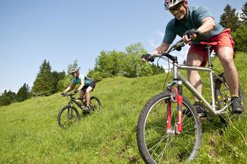 Zwei Bergradler auf einer Wiese