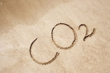The word CO2 handwritten in sand on a beach