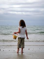 fillette et son seau sur la plage