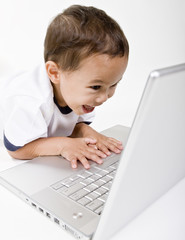 A young boy playing on a laptop computer