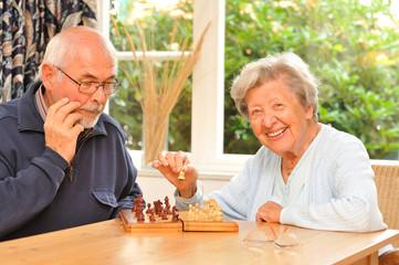 Ein Senior und eine Seniorin spielen Schach III