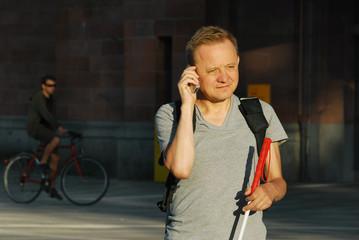 Blinder Mann telefoniert unterwegs