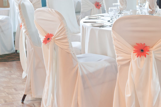 Wedding table with white linen surrounded by covered chairs