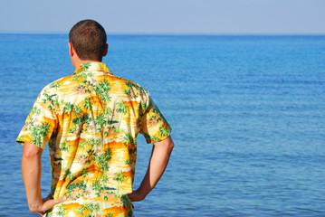 Man in hawaiian shirt looking out to sea
