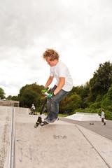 Kinder fahren Roller im Skate Park und üben Tricks