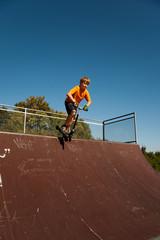 Kind mit Scooter, Roller, übt auf der Skatebahn Tricks