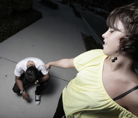 Woman laughing and pointing at the man on the ground