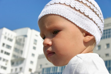 baby boy on a walk on a background white modern building