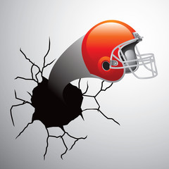 Football helmet coming out of cracked wall